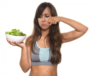 Fitness girl with unhappy face and crying because of she does not like to eat vegetable